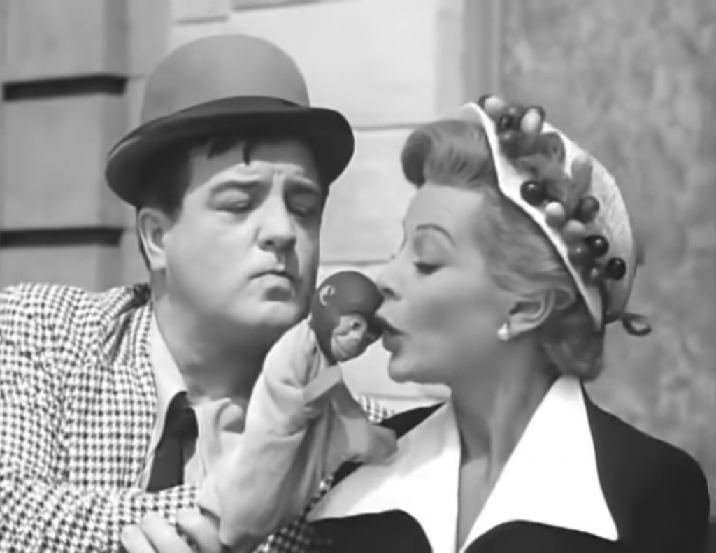 Lou Costello flirting with a pretty young woman on a bench